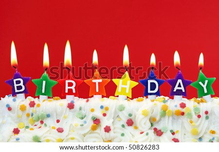 Colorful birthday candles on red background