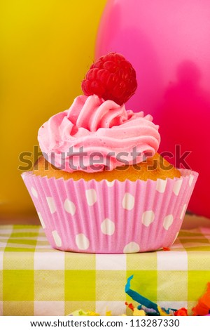 colorful birthday cupcake with confetti and balloons