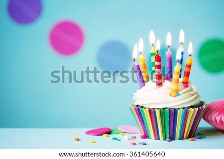 Colorful birthday cupcake with single candle - stock photo