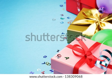 Colorful birthday gift boxes over blue background - stock photo