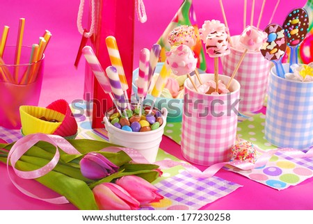colorful birthday party table with flowers,gift and homemade sweets for kids - stock photo