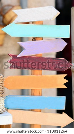 Colorful blank wooden signpost with many arrows - stock photo