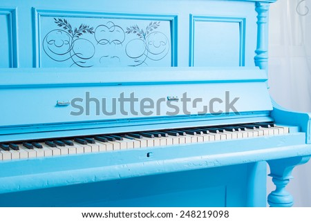 Colorful blue upright piano with the lid open to display the ivories of the keys and keyboard, closeup view showing the scroll work on the front panel - stock photo