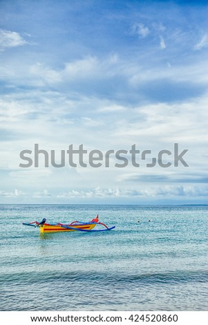 Colorful boat in a clam blue sea with cloud blue skies
