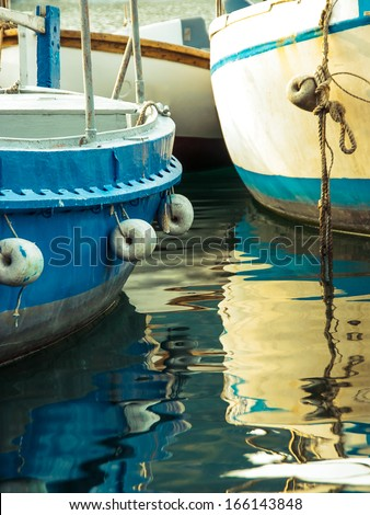 Colorful boats on the pier - fishermans transport. Bow of the fishing boat with reflection on sea surface. Blue motorboats are moored in harbor. - stock photo