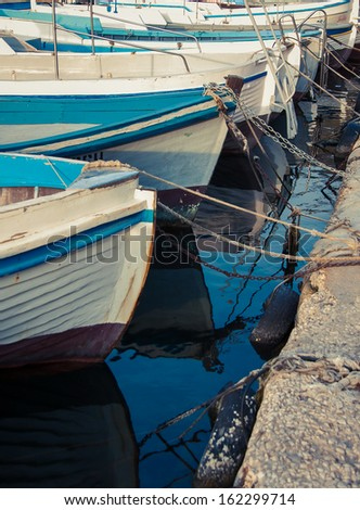 Colorful boats on the pier - water transport. Bow of the fishing boat with reflection on sea surface. Blue motorboats are moored in harbor.