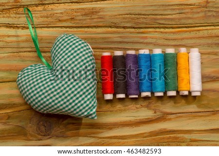 Colorful bobbins of thread with green decorative heart