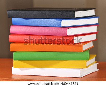 Colorful books on wooden shelf