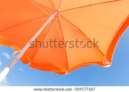 Colorful bottom view of orange parasol against a blue sky