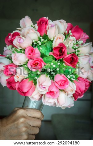 Colorful bouquet of rose made from fabric, Man hand holding bouquet - stock photo