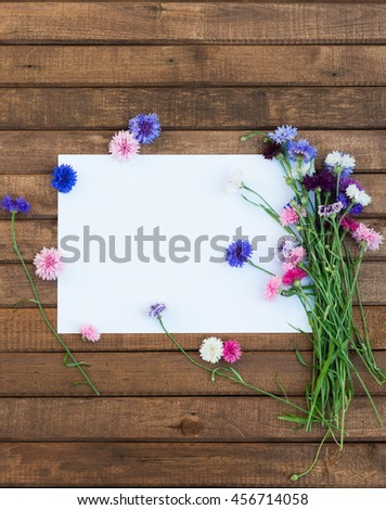 Colorful bouquet of summer garden flowers. Cornflowers with blank paper for greeting message on brown wooden table. Vintage floral background. Floral mock up with multicolored flowers. Copy space - stock photo