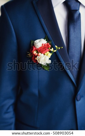 Colorful boutonniere on the blue suit of the groom