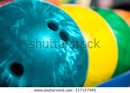 Colorful bowling balls in front of the tenpin alley - stock photo