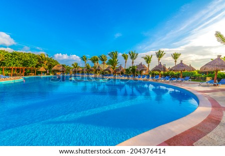 Colorful bridge over swimming pool at the luxury mexican resort,  early morning hours. - stock photo