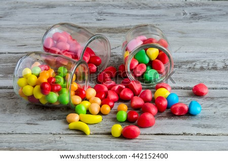 Colorful bright delicious candies scattered on table from jars - stock photo
