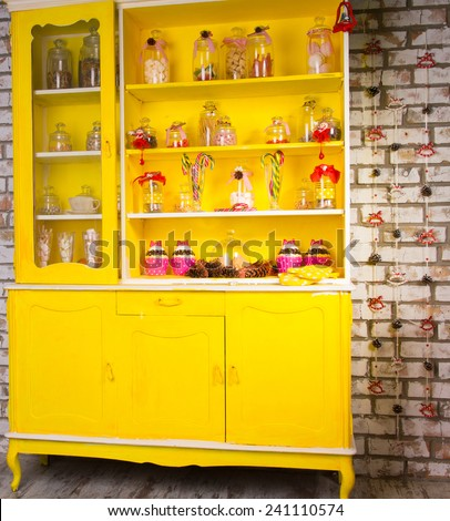 Colorful bright yellow welsh dresser with its shelves filled with decorative glass jars of kitchen ingredients and decorated with striped candy canes and ribbon - stock photo