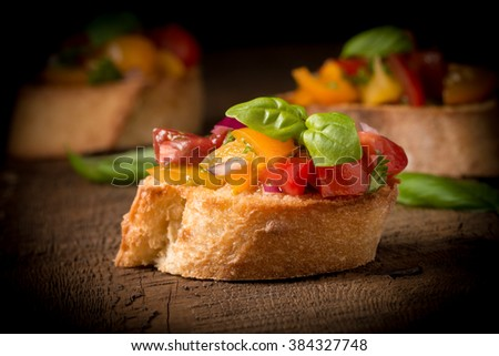 Colorful bruschetta on a rustic background.  Suitable for many food service purposes. - stock photo