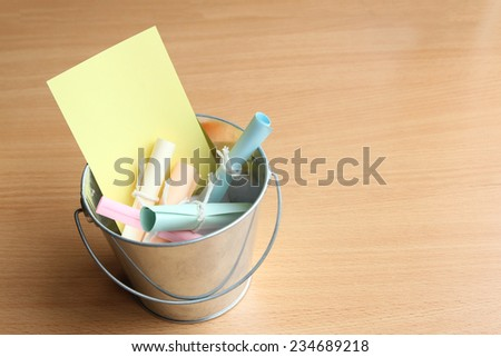 Colorful bucket list on wooden surface - stock photo