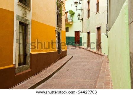 Colorful buildings line a narrow cobblestone street in romantic Guanajuato Mexico -  a World Heritage Site - stock photo