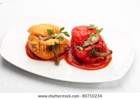 Colorful Bulgarian peppers stuffed with minced meat and rice on a white plate