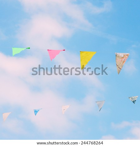 Colorful bunting flags on blue sky with retro filter effect - stock photo