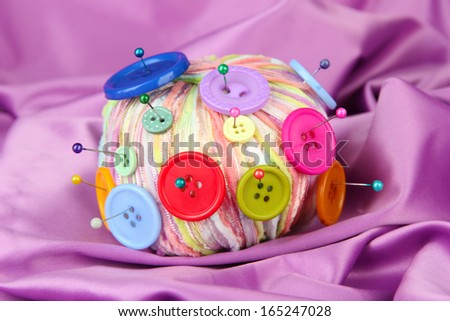 Colorful buttons and multicolor wool ball, on color fabric background - stock photo