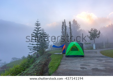 Colorful Camping Tents Mountain and Misty Background in Thailand  - stock photo