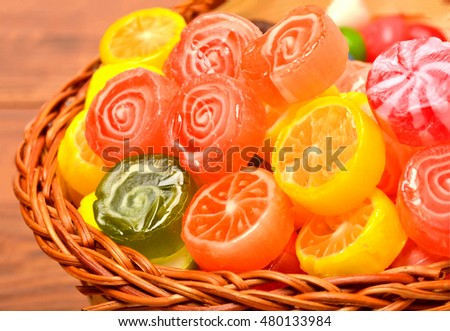 colorful candies and jellies in basket on wooden background