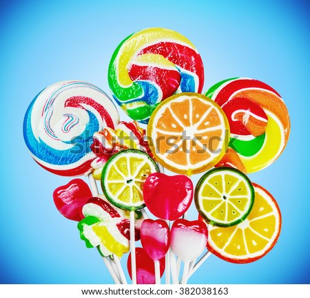 Colorful candies and lollipops on a blue background. focus on large lollipops