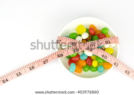 Colorful candies and tape measure with shallow depth of field (dof)-diet and healthy teeth concept - stock photo