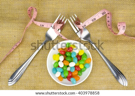 Colorful candies fork and tape measure with shallow depth of field (dof)-diet and healthy teeth concept - stock photo