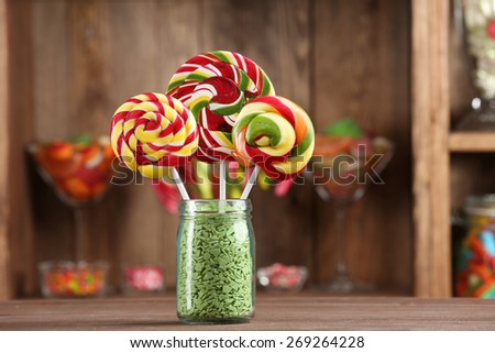 Colorful candies in jar on table in shop - stock photo