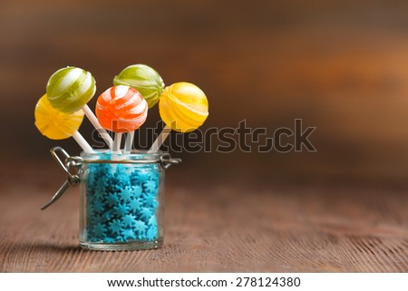 Colorful candies in jar on table on wooden background - stock photo