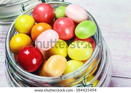 Colorful candies in jar on wooden background. focus on sweets and a glass jar - stock photo