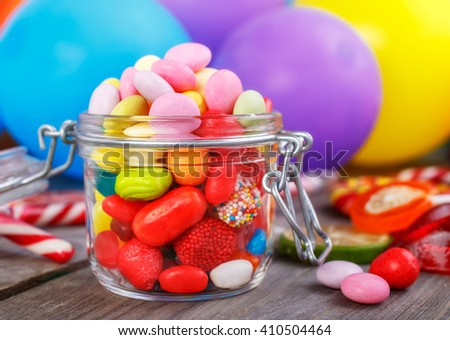 Colorful candies in jar on wooden table against the background colorful balloons - stock photo