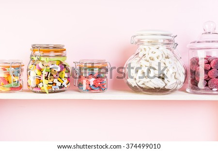 Colorful candies in jars on shelf.