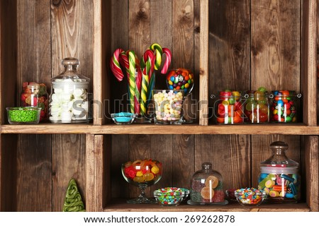 Colorful candies in jars on wooden shelves  close-up - stock photo
