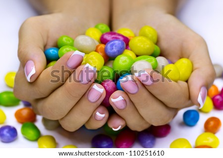 Colorful candies in woman's hands - stock photo