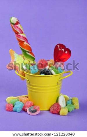 Colorful candies in yellow bucket on purple background