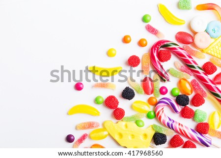 Colorful candies, jellies and lolly pops on the white background. Top view with copy space