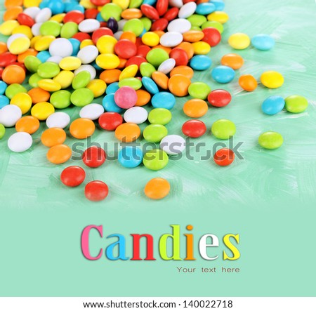 Colorful candies on green background - stock photo