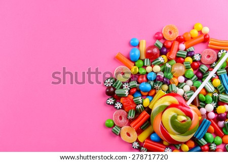 Colorful candies on pink background - stock photo