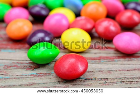Colorful candies on rustic table - stock photo