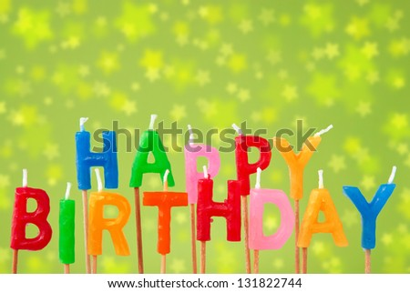 "Colorful candles forming the sentence ""happy birthday"" on the green blurry background - stock photo"