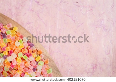 Colorful candy and jelly in dish on pink background - stock photo