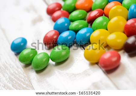 Colorful candy balls on white wooden plank table. Macro shot - stock photo