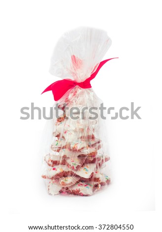 Colorful candy gingerbread Christmas tree with frosting and sugar sprinkles in plastic bag with red ribbon - stock photo