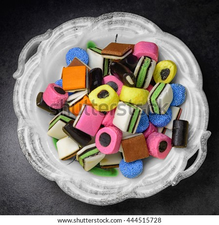 Colorful candy in rustic white dish. Liquorice allsorts in many colors and shapes. Filter effect.