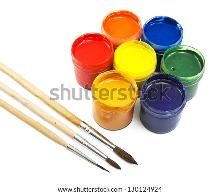 Colorful cans of gouache and brushes on white - stock photo