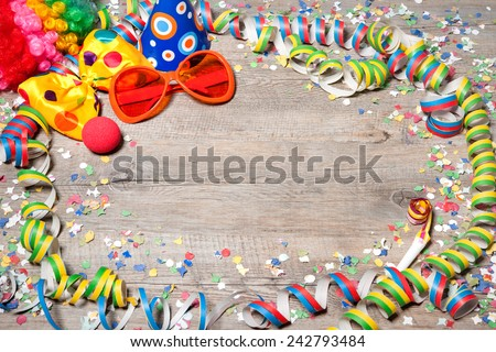 Colorful carnival background with garlands, streamer, party hats, confetti and mask - stock photo